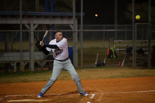 Billy Johnson takes a swing at a ball during a softball game Thursday, Nov. 29, 2018.