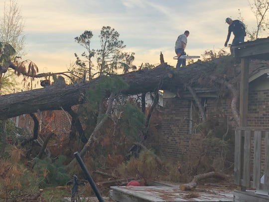 Rodney Braden and Ken Creel volunteer to remove a fallen tree after Hurricane Michael in Altha.