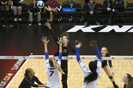 Seminoles setter Adrian Ell (17) hits the ball over her blockers. Florida State was swept 3-0 by the Florida Gators during the first round of the NCAA Volleyball Tournament Thursday, Nov. 29, 2018 in Orlando.