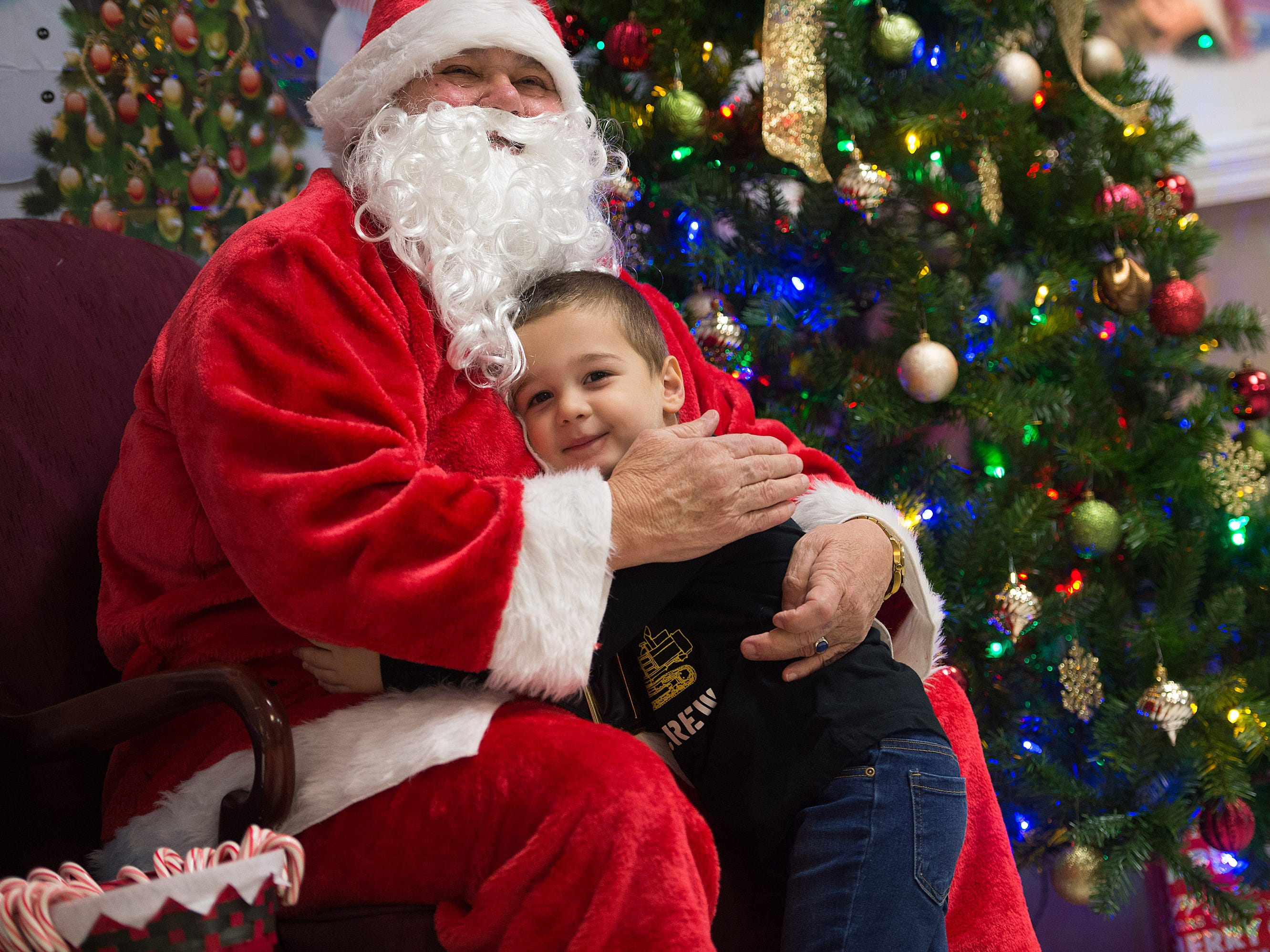 "Vincenzo Roscello, 3, of Port St. Lucie, hugs Santa Claus during the Firehouse Youth Centre's Breakfast with Santa fundraiser event at the Firehouse Youth Centre on Friday, November 30, 2018 in Port St. Lucie. ""I want a monster truck with batteries and a remote control,"" said Roscello adding, ""I like Santa."" The event was held as a fundraiser for families in need over the holidays."