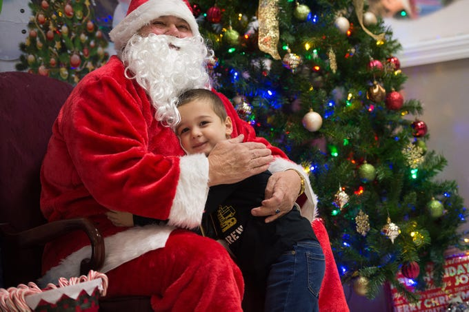 """Vincenzo Roscello, 3, of Port St. Lucie, hugs Santa Claus during the Firehouse Youth Centre's Breakfast with Santa fundraiser event at the Firehouse Youth Centre on Friday, November 30, 2018 in Port St. Lucie. """"I want a monster truck with batteries and a remote control,"""" said Roscello adding, """"I like Santa."""" The event was held as a fundraiser for families in need over the holidays."""