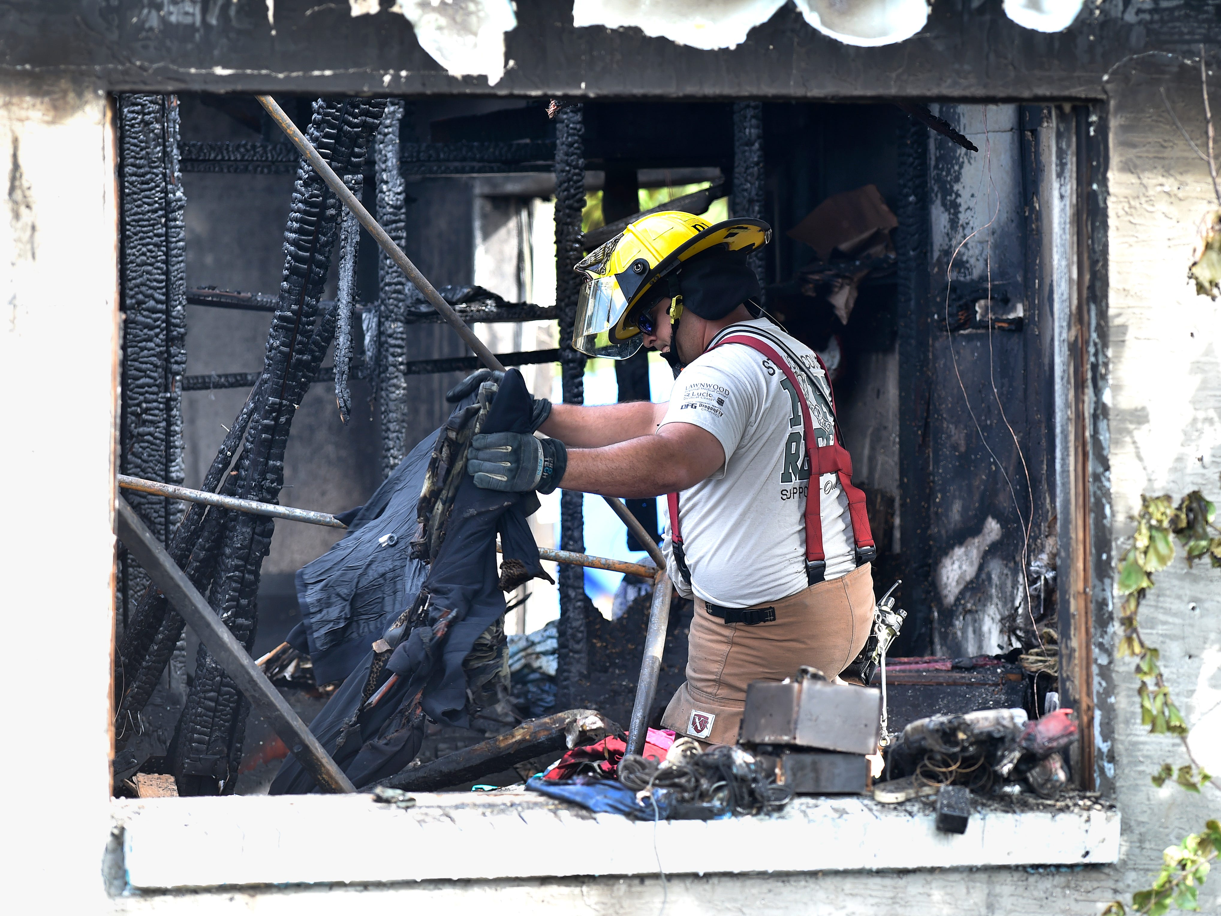 One of several St. Lucie County Fire District firefighters sorts through remains inside a home in the 2800 block of Avenue B on Friday, Nov. 30, 2018, during the investigation of the fire that completely destroyed the house shortly after 2 a.m., in Fort Pierce.