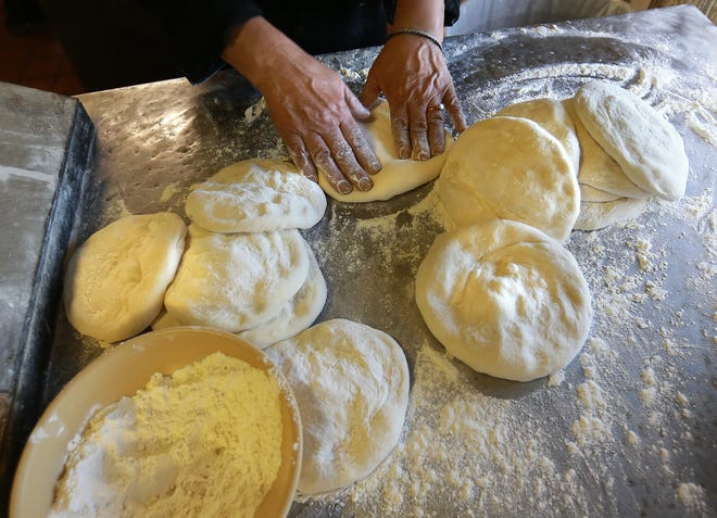 The Italian Kitchen cook Yolanda Zavala makes pizza crust in the restaurant Thursday.