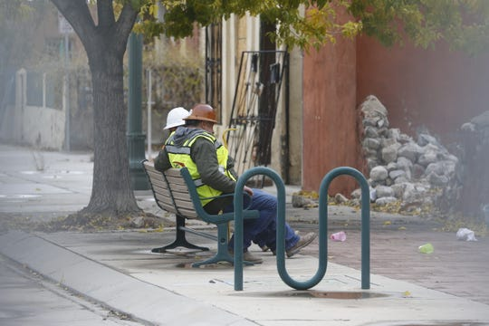 Workers take a break Friday in the closed-off section of the Duranguito neighborhood.