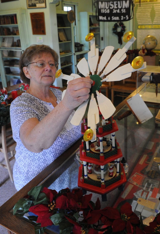 Docent Karen Schemm sets up Christmas decorations in the library at Strathearn Historical Park and Museum. Holiday in the Park will be held Sunday.