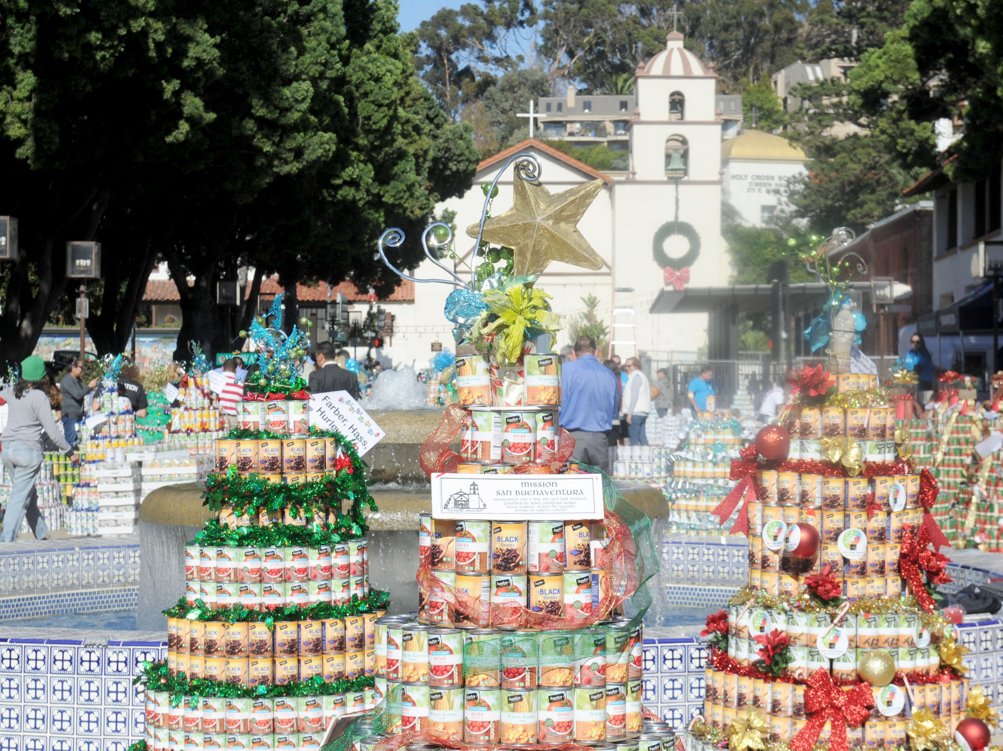 Mission San Buenaventura serves as a backdrop for can trees being built as part of FOOD Share's annual CAN-tree drive in downtown Ventura at Figueroa Plaza.