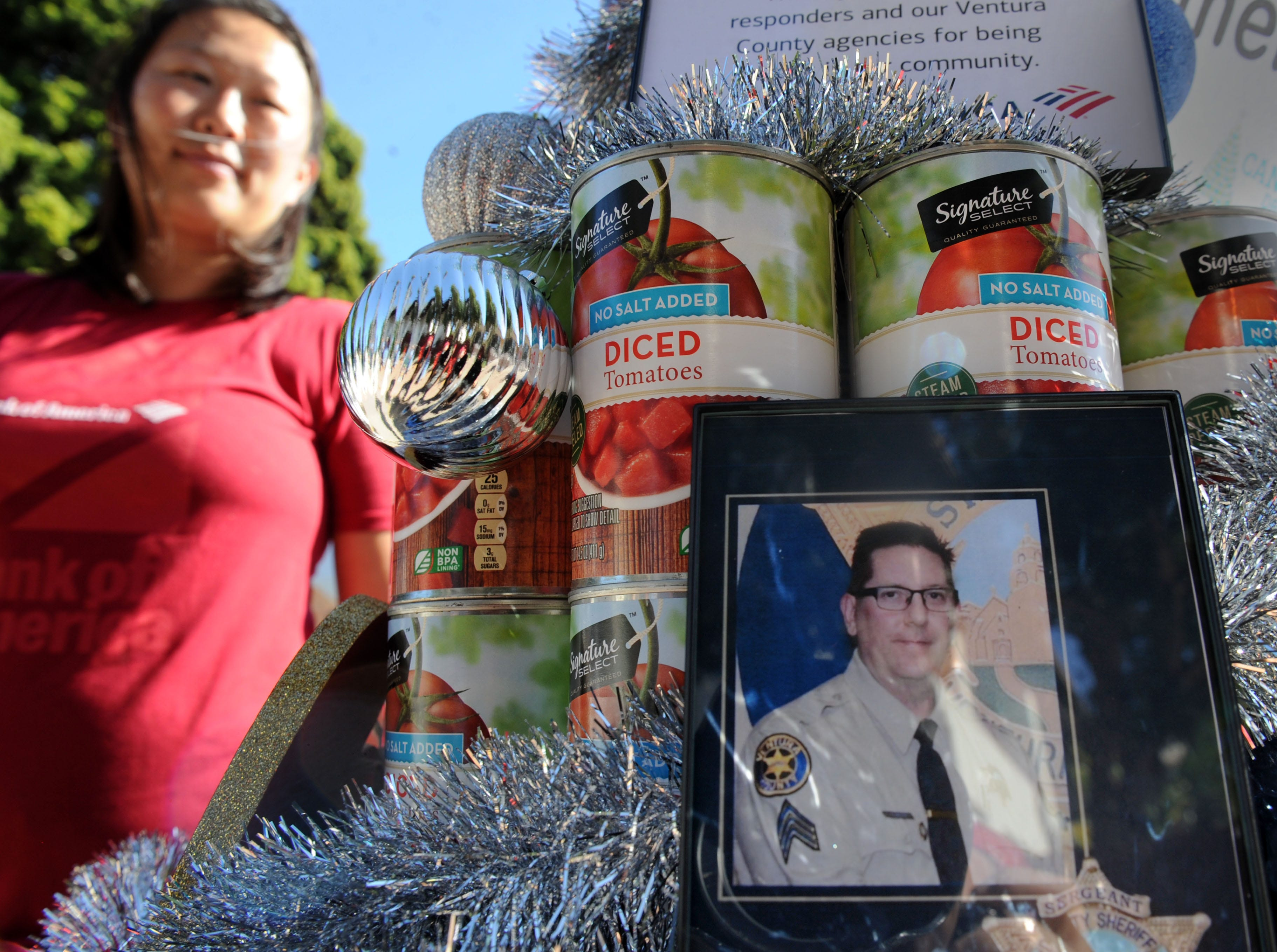Michelle Yee, senior vice president and Ventura/Santa Barbara market manager at Bank of America, pays tribute to Ventura County sheriff's Sgt. Ron Helus, who was killed at the Borderline Bar & Grill in Thousand Oaks, by putting his photos around her can tree at FOOD Share's annual CAN-tree food drive in downtown Ventura at Figueroa Plaza.