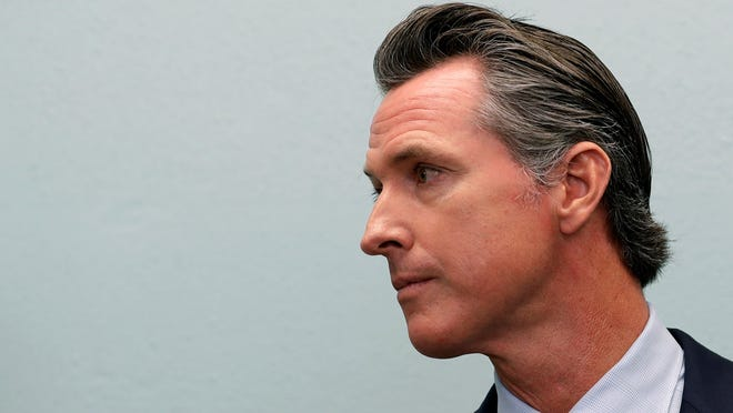 Gov.-elect Gavin Newsom looks on during a news conference near the border Thursday in San Diego. Newsom was scheduled to meet with organizations aiding asylum seekers and to tour a nearby immigration detention center before heading to Mexico City for the inauguration of Mexico's next president, Andres Manuel Lopez Obrador, this weekend.