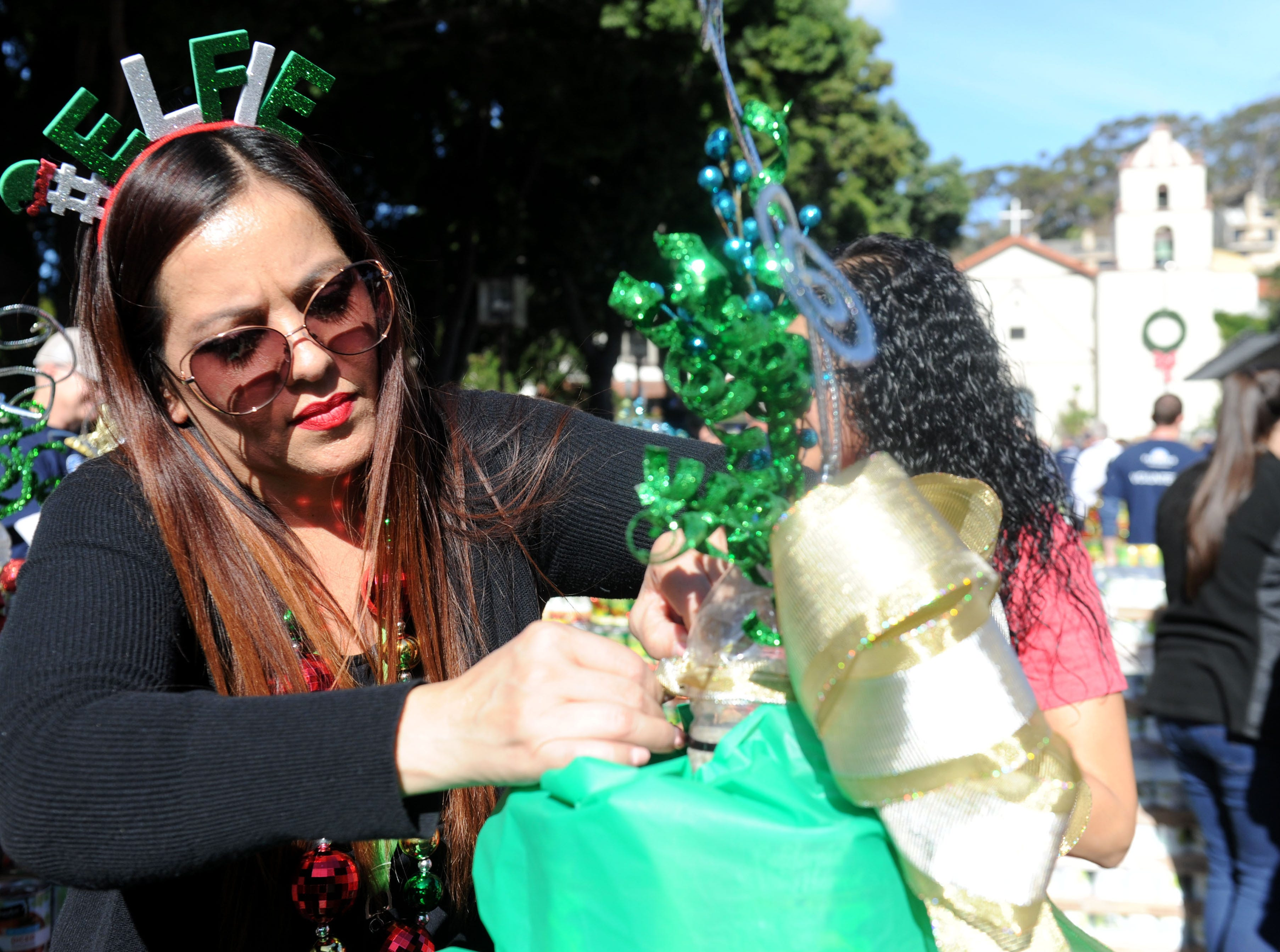 Sonia Lopez, supervisor for Ventura County Department of Child Support  Services, puts the finishing touches on a tree at FOOD Share's annual CAN-tree drive in downtown Ventura at Figueroa Plaza.