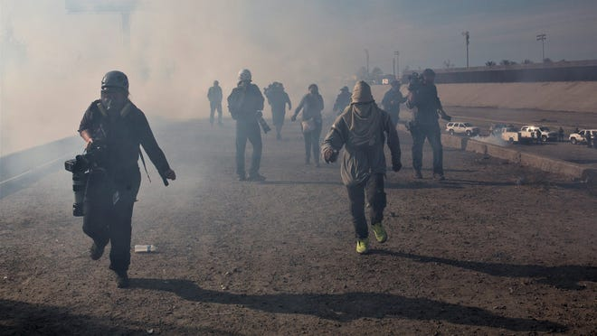 Migrants run from tear gas launched by U.S. agents, amid photojournalists covering the Mexico-U.S. border, after a group of migrants got past Mexican police at the Chaparral crossing in Tijuana on  Sunday.