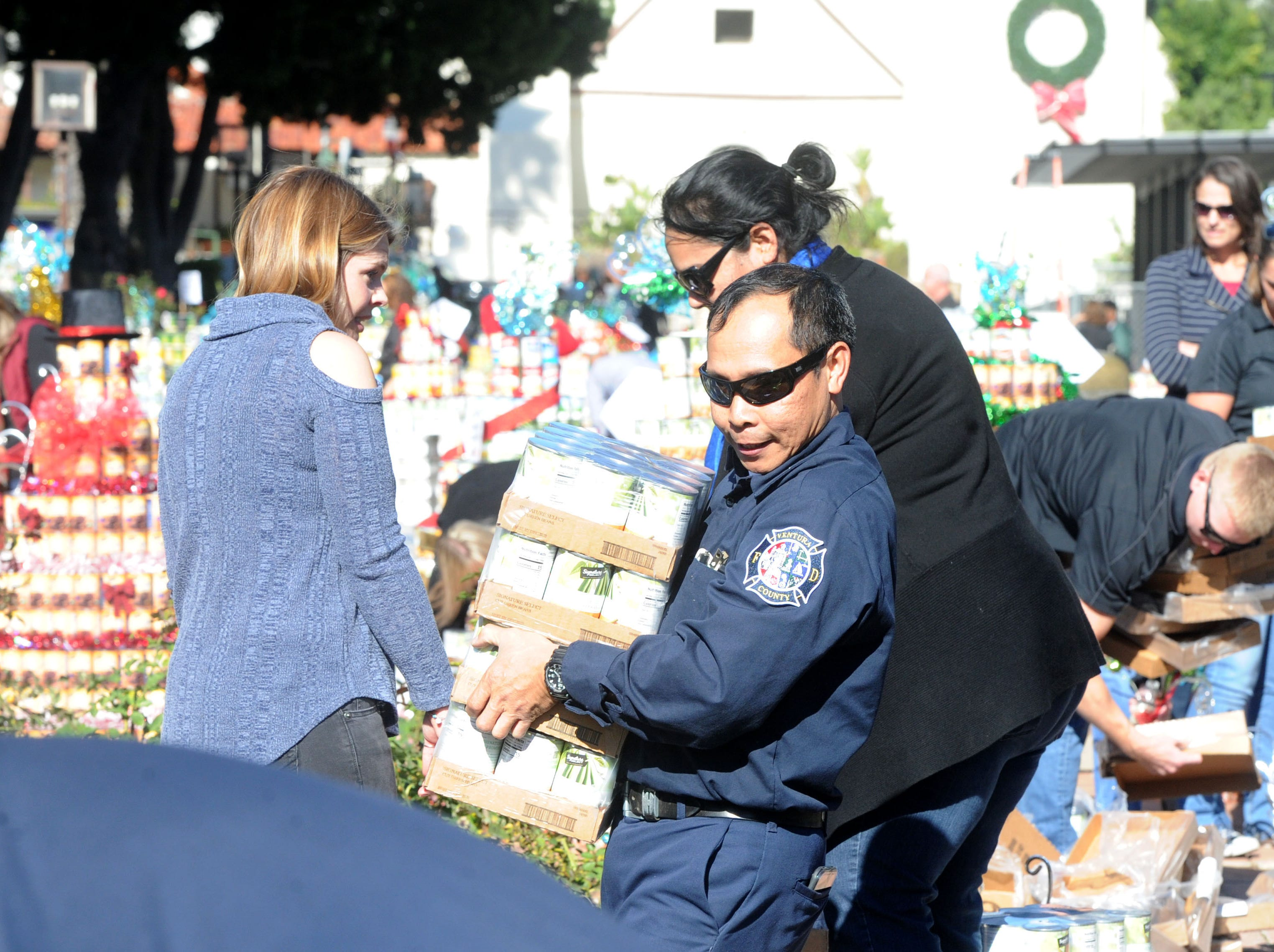 Rene Nera, telecommunications network specialist at the Ventura County Fire Department, helps carry cans to a can tree being built at FOOD Share's annual CAN-tree drive in downtown Ventura at Figueroa Plaza. Hero Rowwas reserved for first responders, who came out to be a part of the drive.