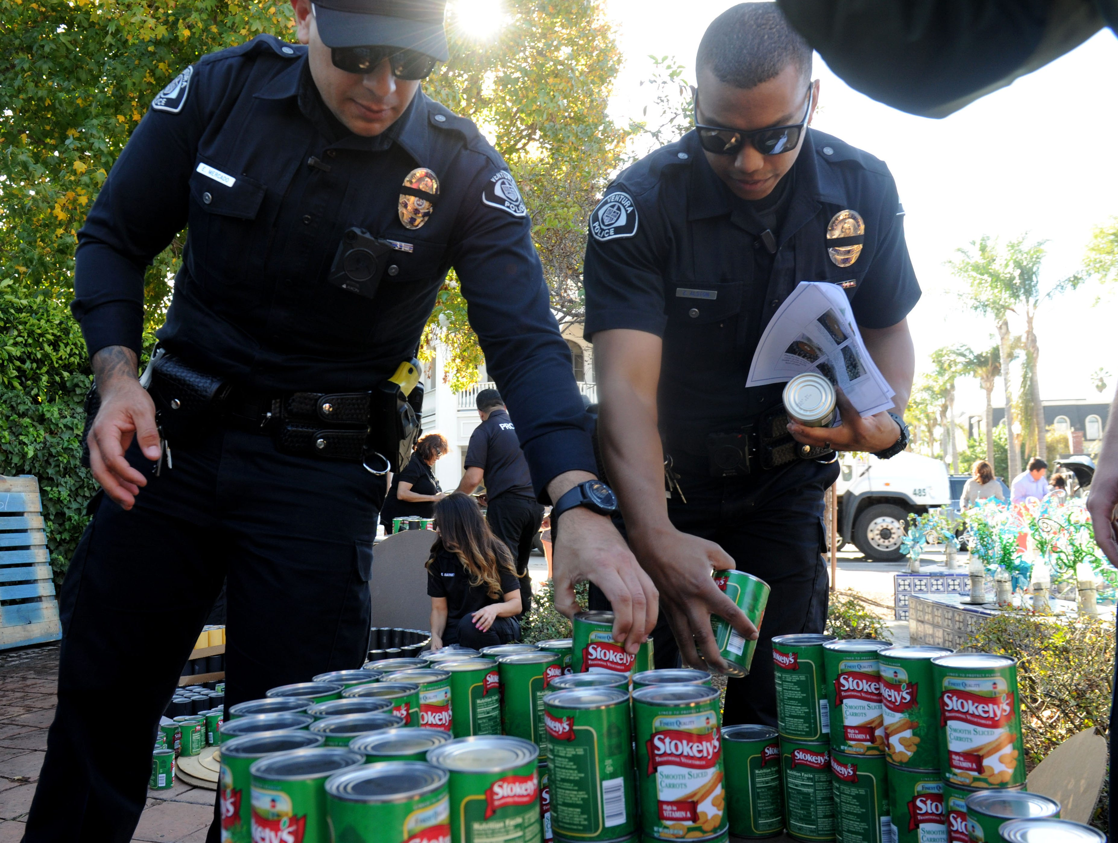 Ventura police officers Emerson Mercado, left, and Zane Alston help build a tree out of cans of food at FOOD Share's annual CAN-tree food drive in Downtown Ventura at Figueroa Plaza. Hero Row was reserved for first responders.