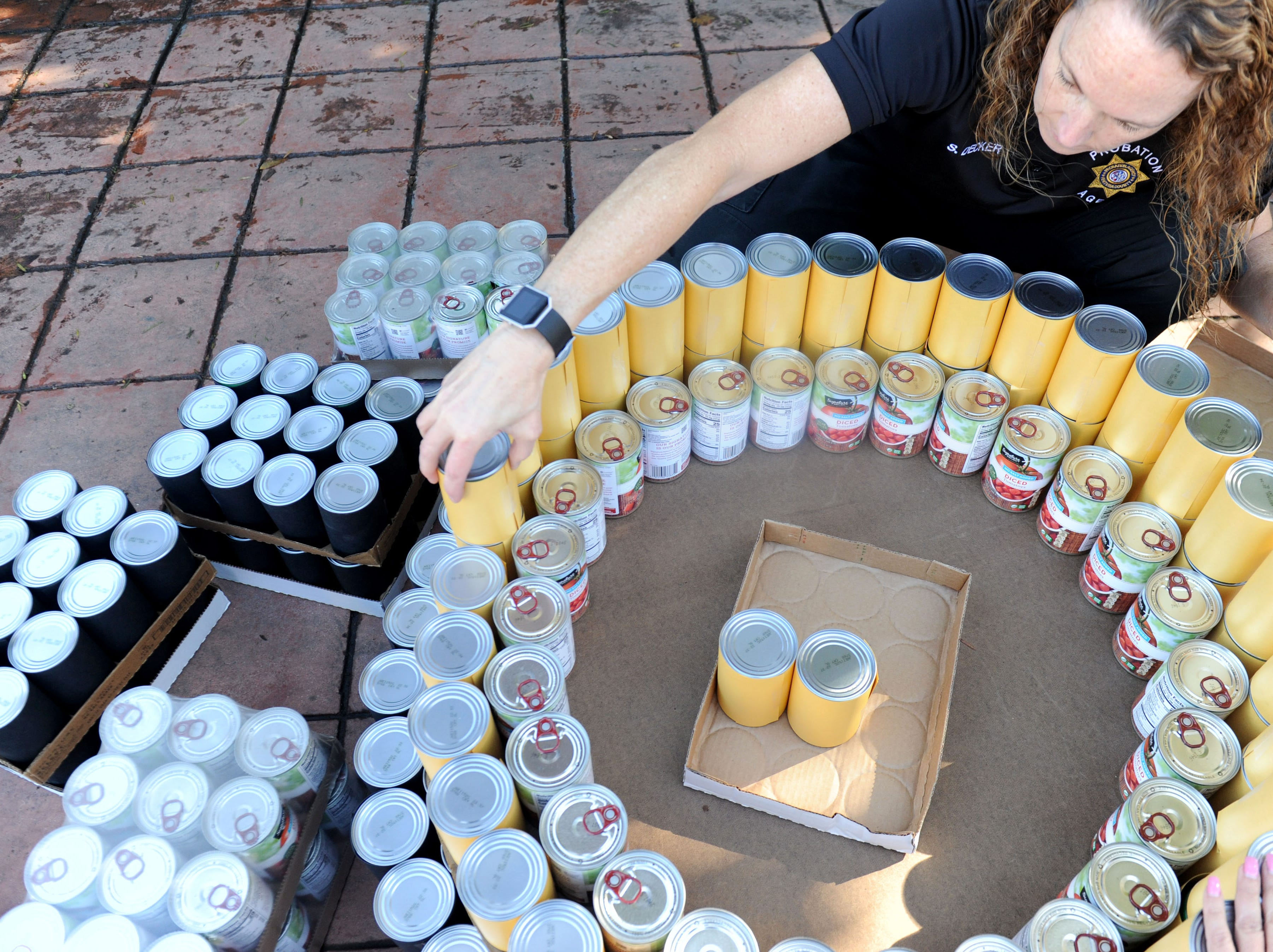 Shana Decker, senior deputy probation officer for the County of Ventura helps build a can tree at FOOD Share's annual CAN-tree food drive in downtown Ventura at Figueroa Plaza.