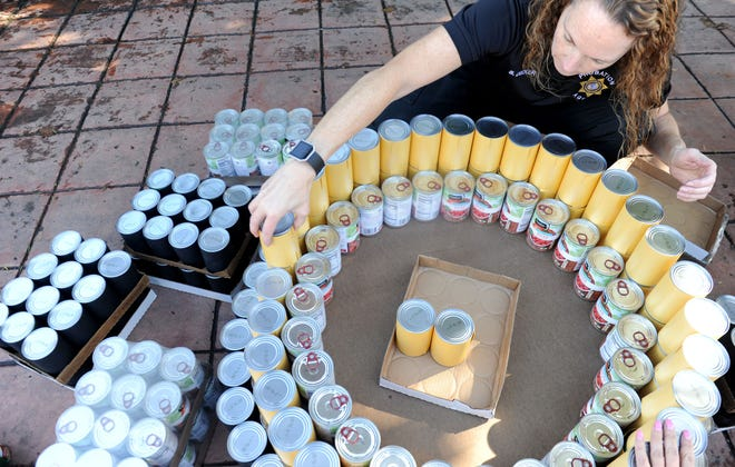 Shana Decker, a senior deputy probation officer for the County of Ventura, helps build a can tree at Food Share's 2018 CAN-tree food drive in downtown Ventura at Figueroa Plaza.
