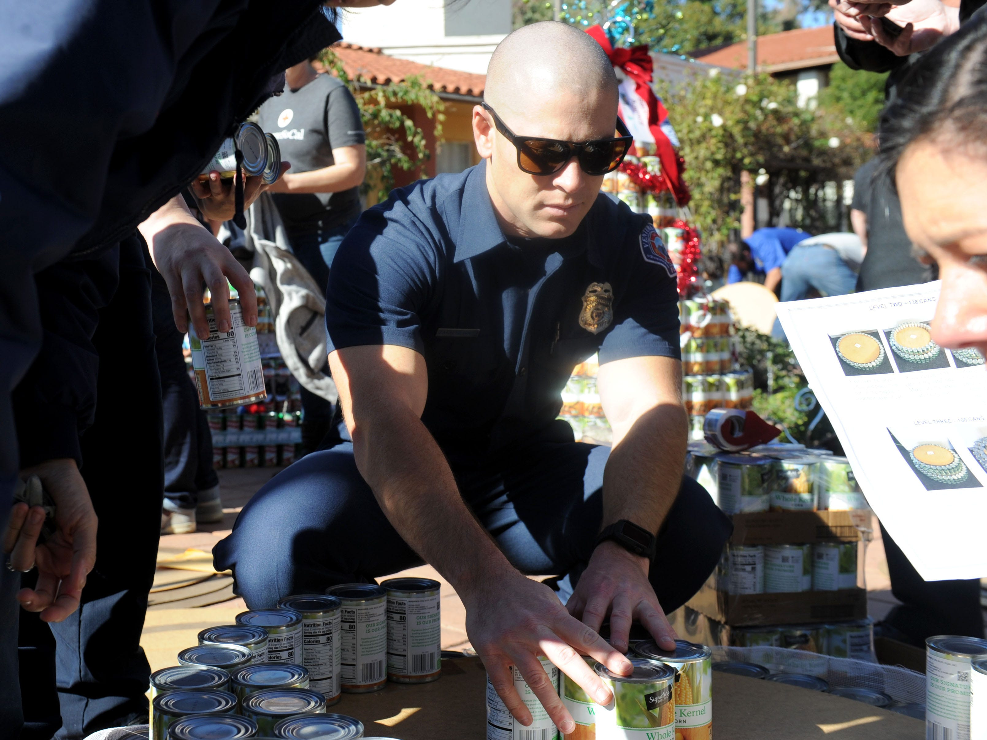 Zach Benner, a Ventura city firefighter, helps build a can tree at FOOD Share's annual CAN-tree drive in downtown Ventura at Figueroa Plaza. Hero Rowwas reserved for first responders, who came out to be a part of the drive.