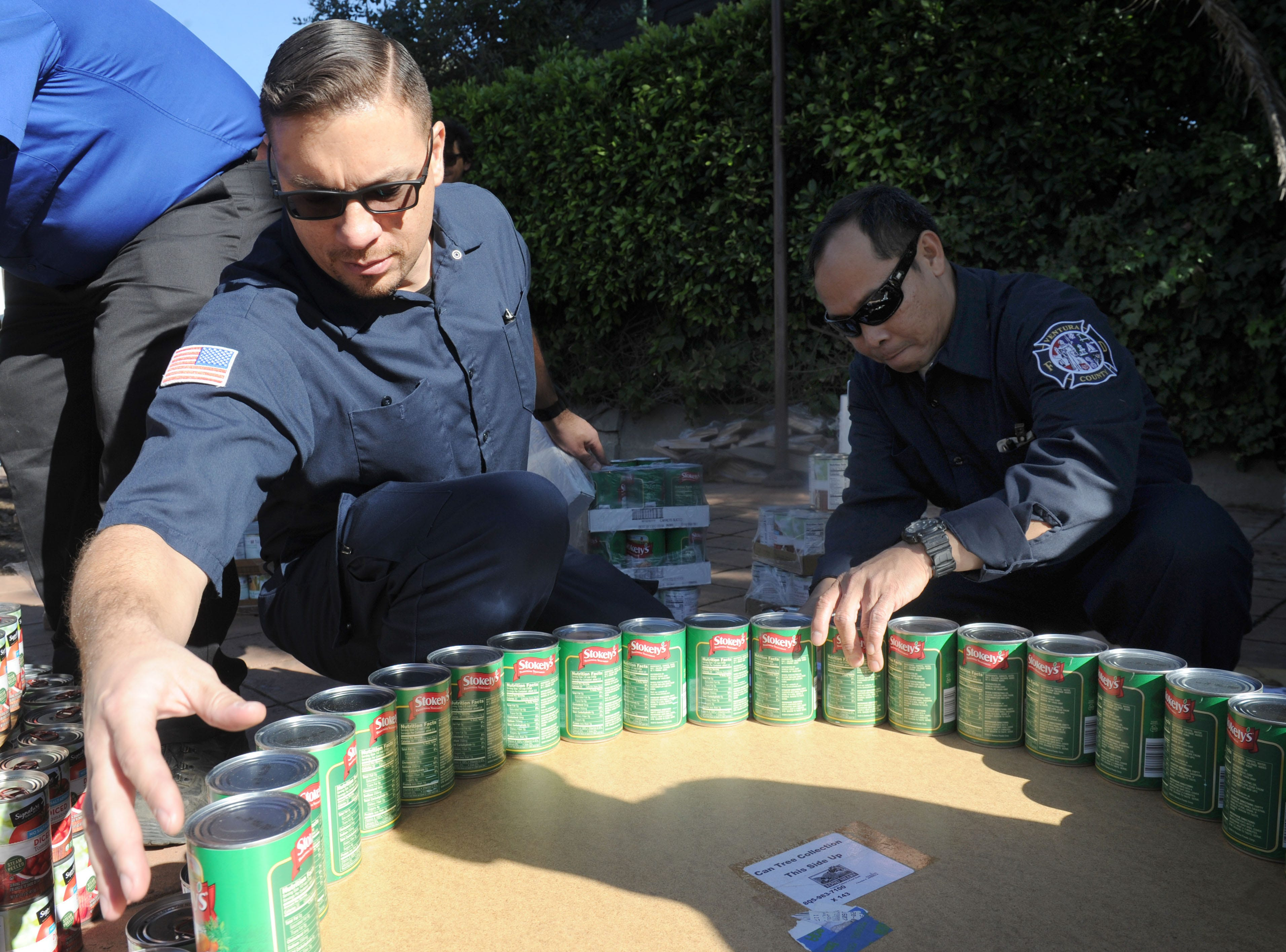 Carl Varvaro, left, and Rene Nera, both telecommunications network specialists at the Ventura County Fire Department,  help build a can tree at FOOD Share's annual CAN-tree drive in downtown Ventura at Figueroa Plaza.