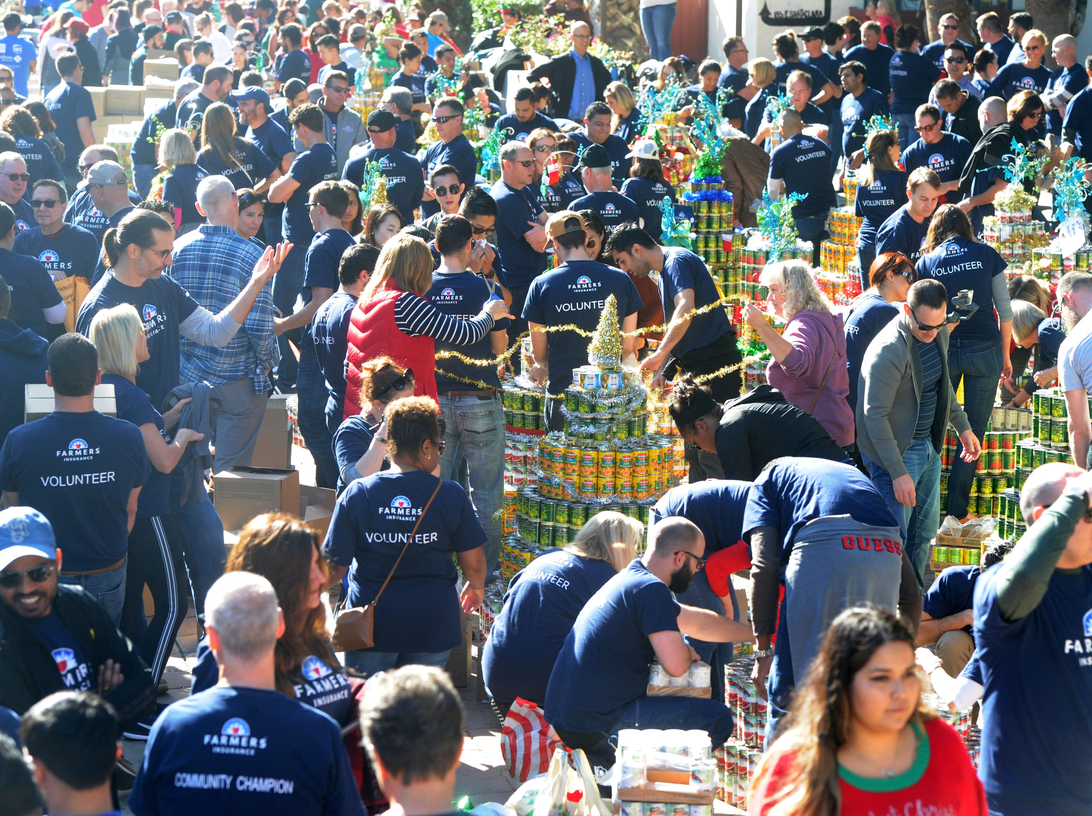 Volunteers from various organizations help build the can trees at FOOD Share's annual CAN-tree food drive in downtown Ventura at Figueroa Plaza.