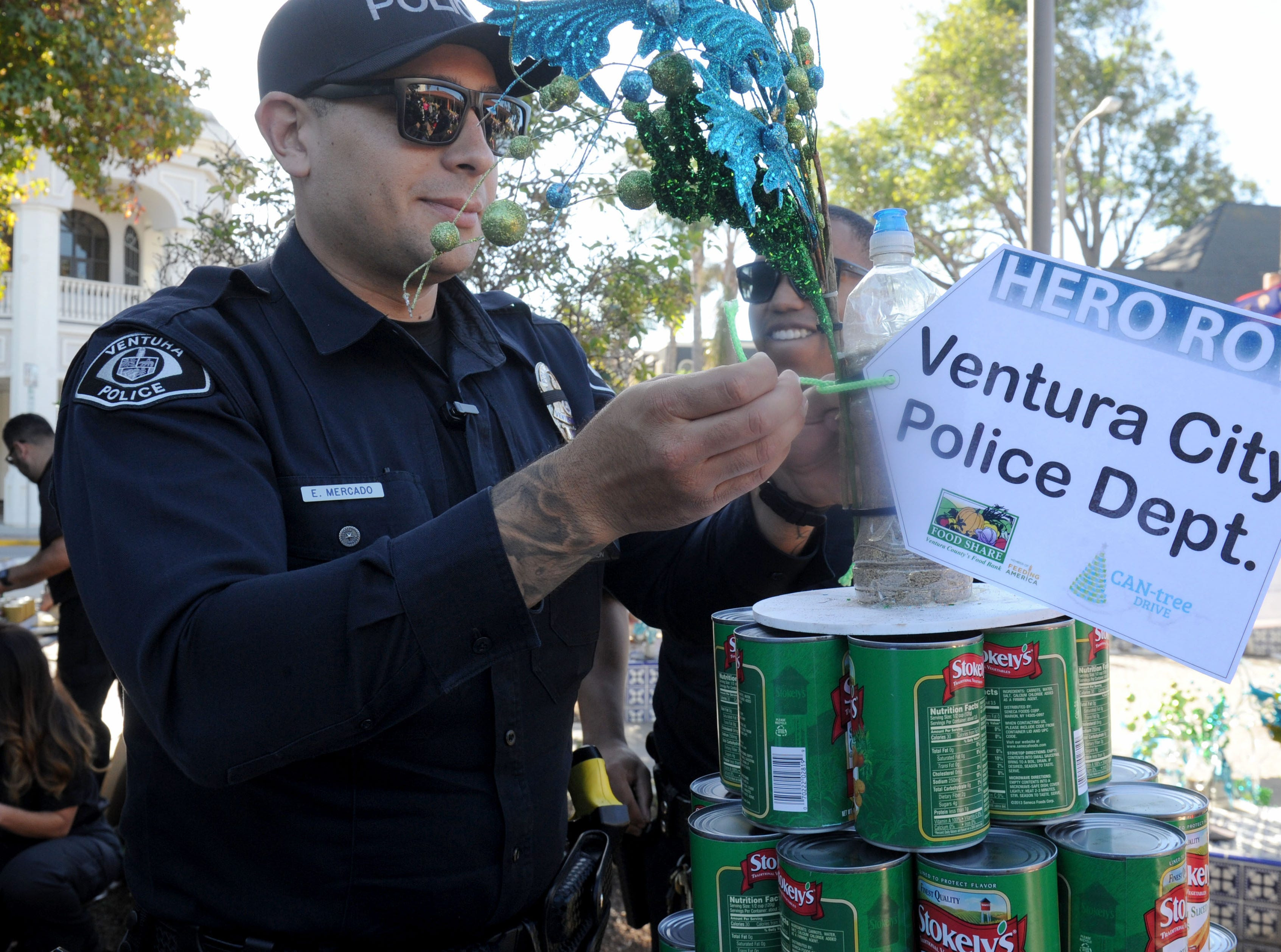 Ventura Police Officers Emerson Mercado, left, and Zane Alston add the last piece to their can tree at FOOD Share's annual CAN-tree drive in downtown Ventura at Figueroa Plaza.