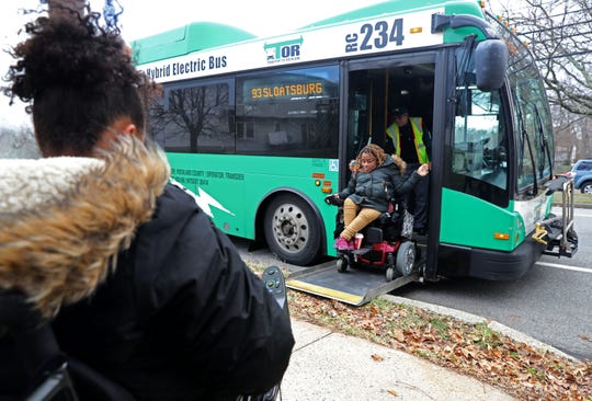 Zasia Davis, 22, looks on as her sister Diana Bouknight, 28, is assisted off the bus as they head home after work in Nov. 27, 2018 Spring Valley. Both use wheelchairs and the bus is their only means of transportation.