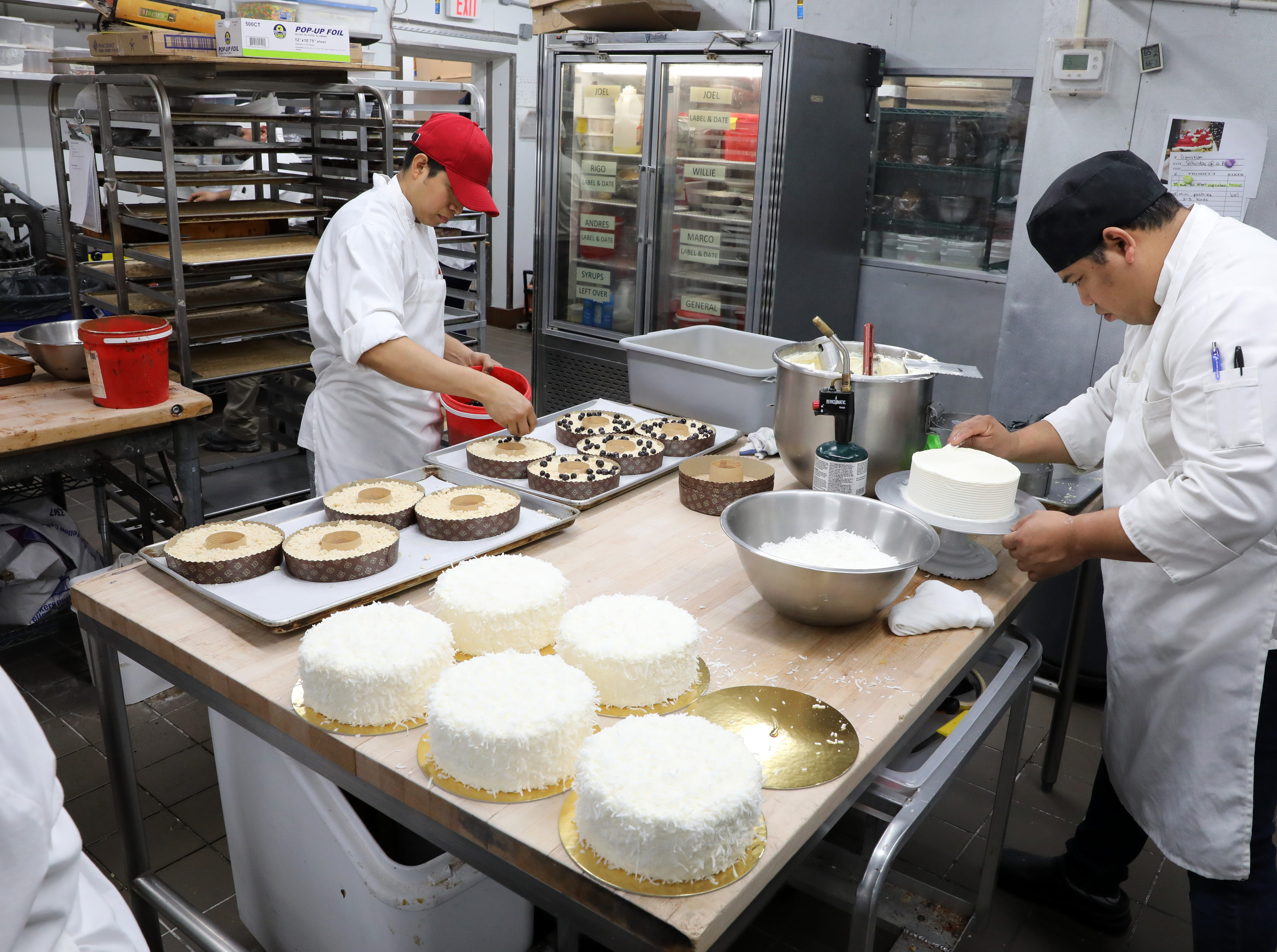 Marco Retana, left, prepares blueberry lemon coffee cake as his brother, Wilfredo Retana, decorates a coconut cake at Martine's Fine Bake Shoppe in Tuckahoe Nov. 29, 2018. The family bakery, which has a second location in Scarsdale, is celebrating their 10th anniversary in business.
