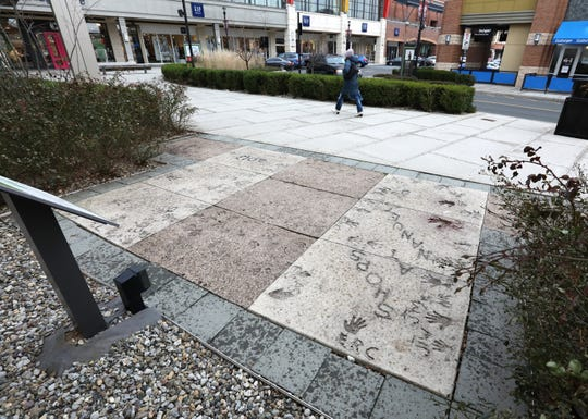 A shopper walks by handprints in concrete at The Shops at Nanuet Nov. 30, 2018. The lighter ones were done in 2013, in center are handprints from Bamberger's opening in 1969.