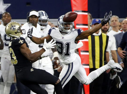 Dallas Cowboys cornerback Byron Jones (31) breaks up a pass intended for New Orleans Saints wide receiver Michael Thomas (13) during the second half of an NFL football game, in Arlington, Texas, Thursday, Nov. 29, 2018. Jones was called for interference on the play.