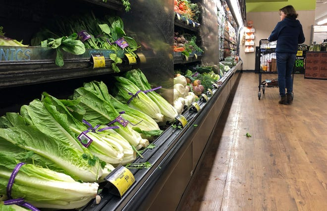 FILE - In this Nov. 20, 2018 file photo, romaine lettuce sits on the shelves as a shopper walks through the produce area of an Albertsons market in Simi Valley, Calif.  After repeated food poisoning outbreaks linked to romaine lettuce, the produce industry is confronting the failure of its own safety measures in preventing contaminations. The latest outbreak underscores the challenge of eliminating risk for vegetables grown in open fields and eaten raw. It also highlights the role of nearby cattle operations and the delay of stricter federal food safety regulations.