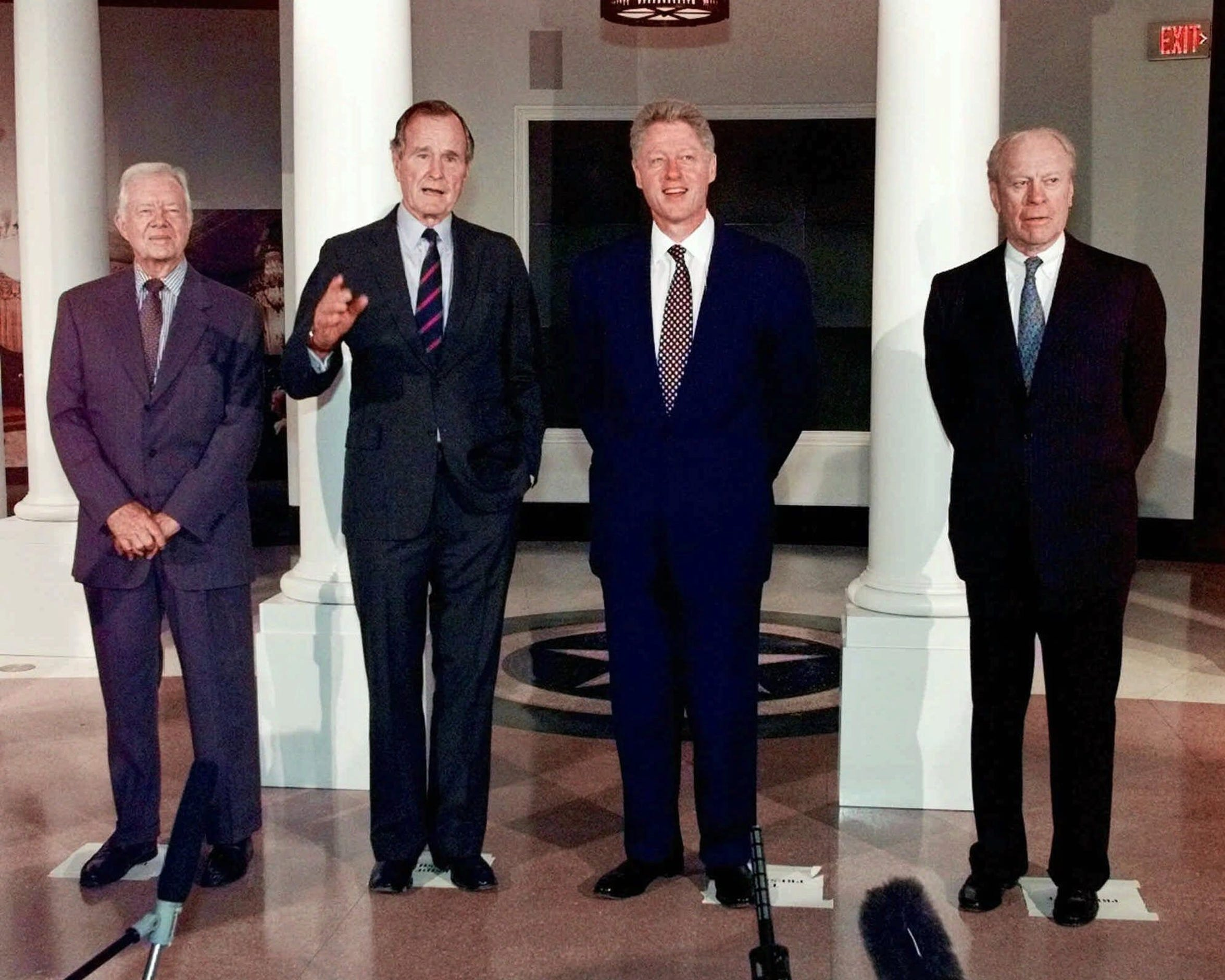Former Presidents Jimmy Carter, George H. W. Bush and Gerald R. Ford join then President Clinton in front of exhibit at the George Bush Presidential Library in 1997.