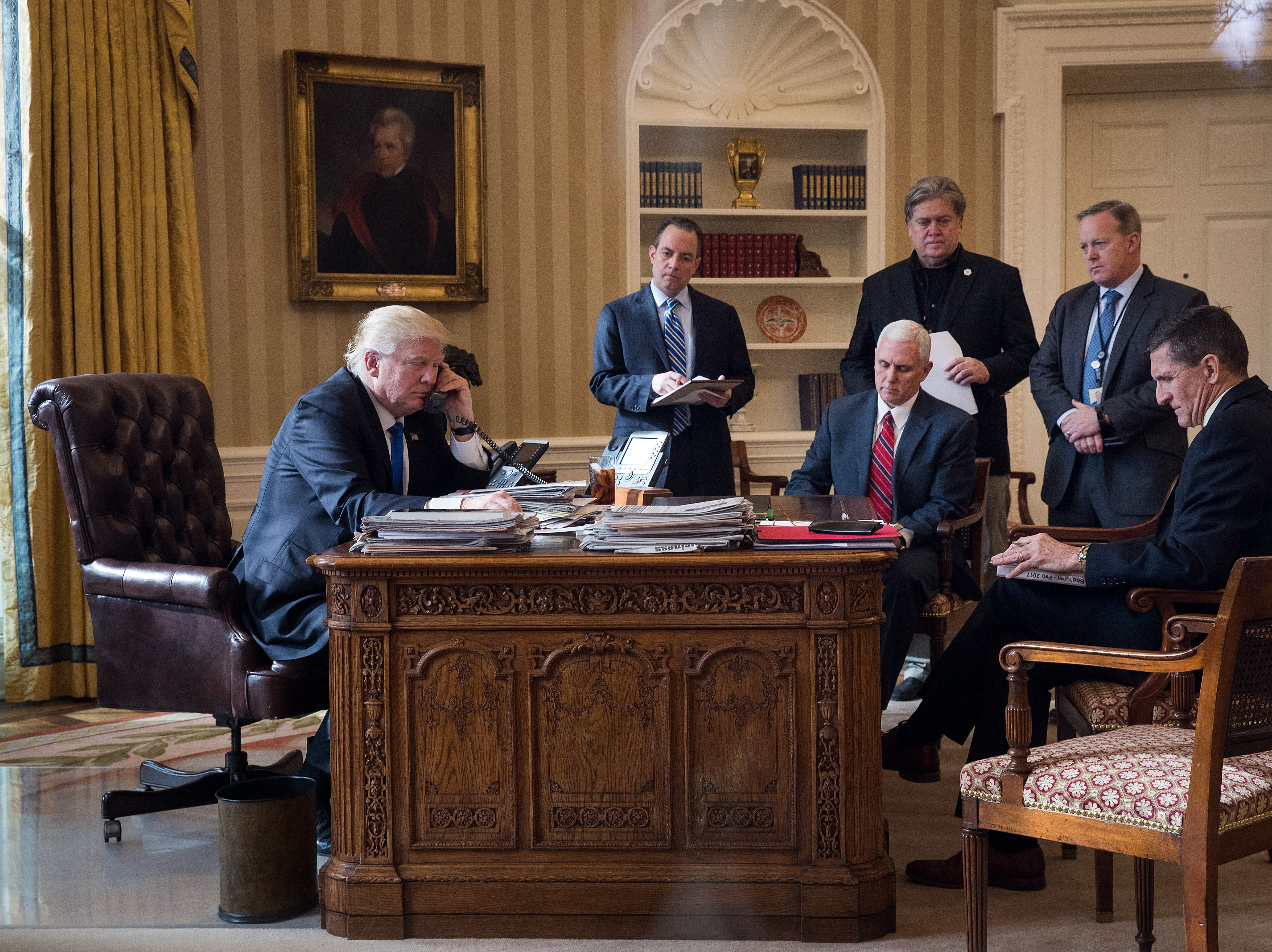 President Donald Trump speaks on the phone with Russian President Vladimir Putin in the Oval Office of the White House, Jan. 28, 2017 in Washington, DC. Also pictured, from left, White House Chief of Staff Reince Priebus, Vice President Mike Pence, White House Chief Strategist Steve Bannon, Press Secretary Sean Spicer and National Security Advisor Michael Flynn. On Saturday, President Trump is making several phone calls with world leaders from Japan, Germany, Russia, France and Australia.