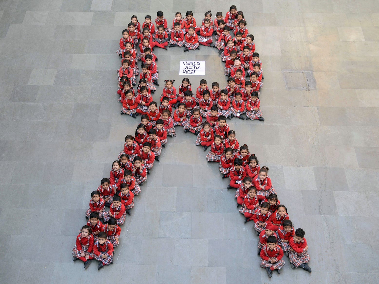 Indian school students pose for a photograph as they sit in the shape of a ribbon on the eve of World AIDS Day in Amritsar. World AIDS Day has been observed on Dec. 1 since 1988 to raise awareness of the AIDS pandemic. Click ahead to view World AIDS Day through the years.