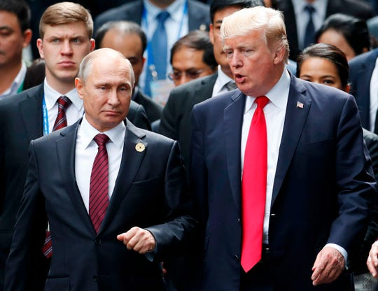 "US President Donald Trump, right, and Russian President Vladimir Putin talk as they make their way to take the ""family photo"" during the Asia-Pacific Economic Cooperation (APEC) leaders' summit in the central Vietnamese city of Danang on Nov. 11, 2017."