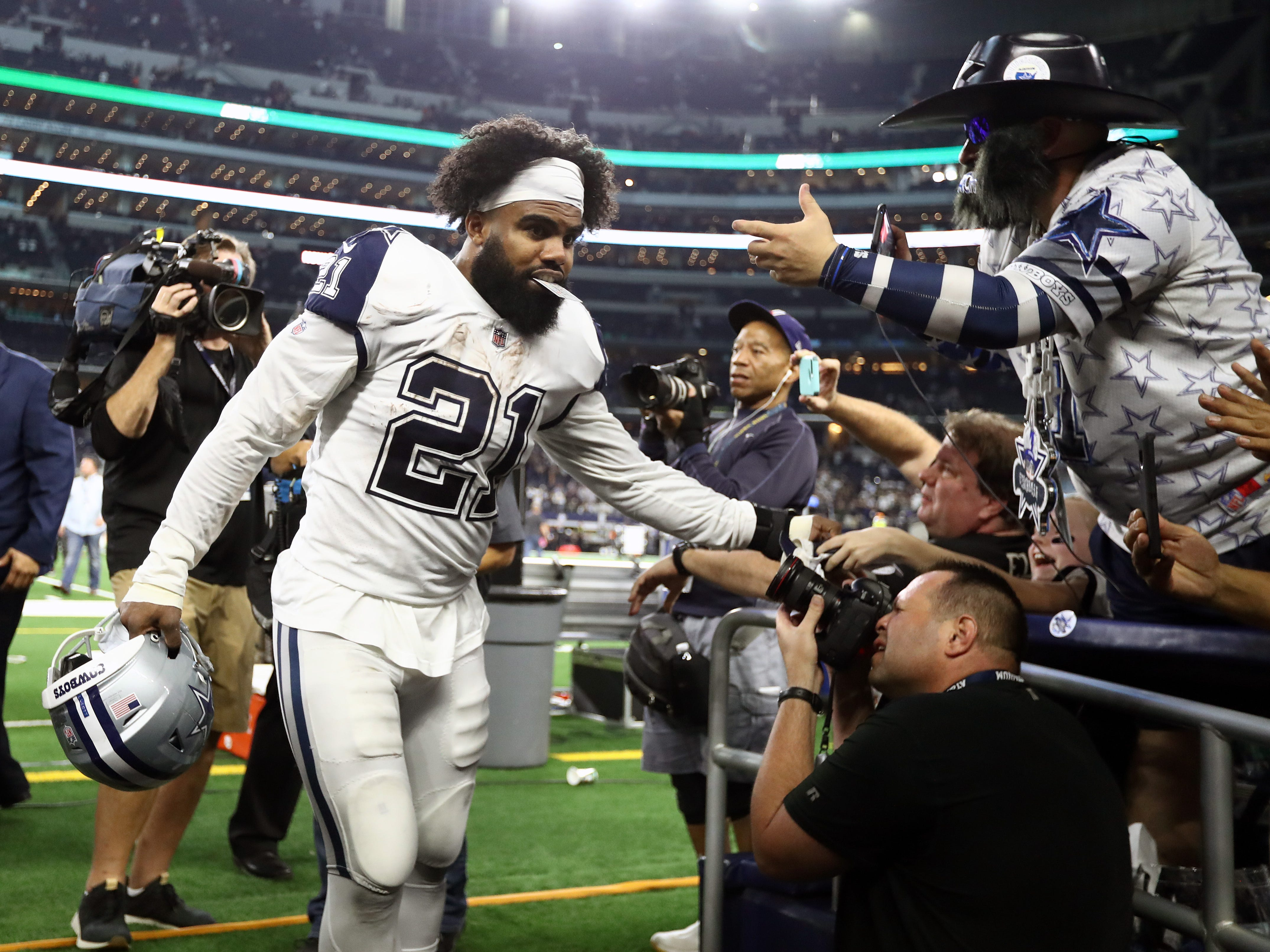 Dallas Cowboys running back Ezekiel Elliott celebrates with fans after a victory against the New Orleans Saints at AT&T Stadium.