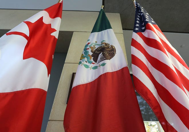 U.S., Mexican, and Canadian flags are pictured sitting in a lobby in Ottawa, Ontario.