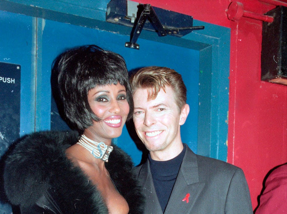 "British rock singer David Bowie and his wife, supermodel Iman, are seen backstage at the Prince of Wales ""Concert of Hope"" to mark World AIDS Day at London's Wembley Arena, in 1993."