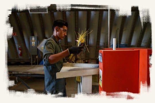Un trabajador de Green America Recycling & Recovery lleva un puñado de cables a una máquina de pulir para demostrar cómo se cortan y reciclan los cables.