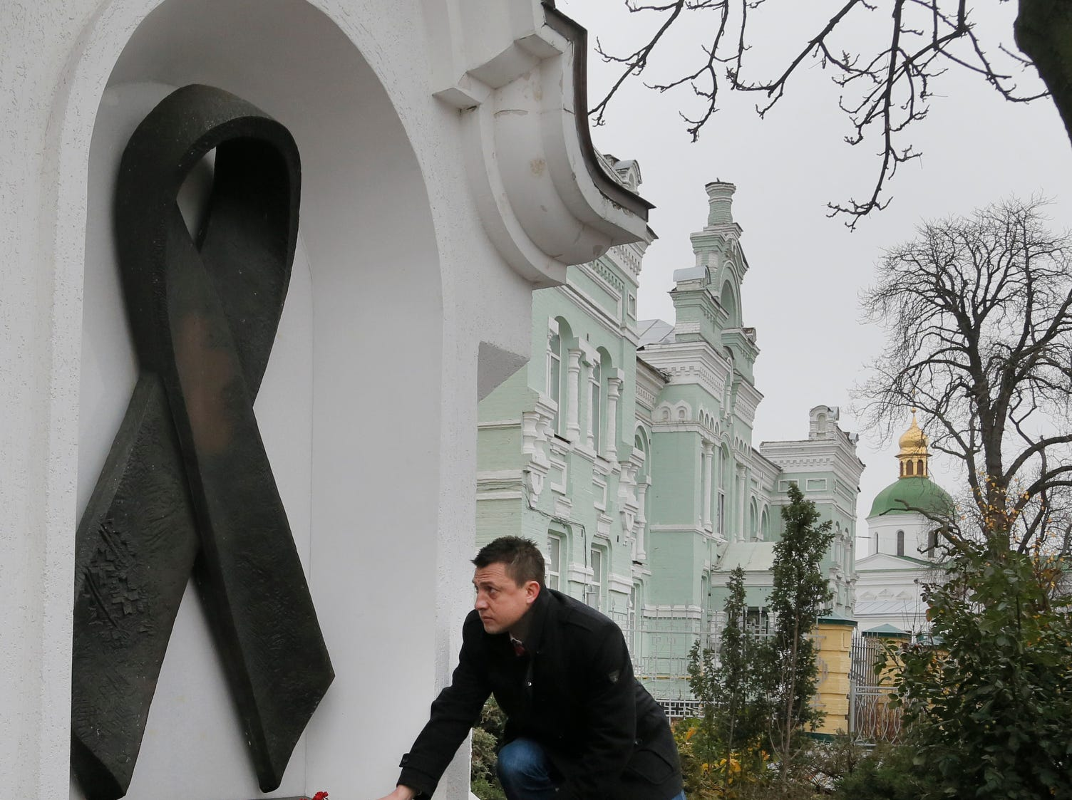 A man lays flowers at the memorial monument dedicated to AIDS victims, to mark the World AIDS Day and in memory of those who have died of AIDS in Kiev, Ukraine, on Dec. 1, 2015.