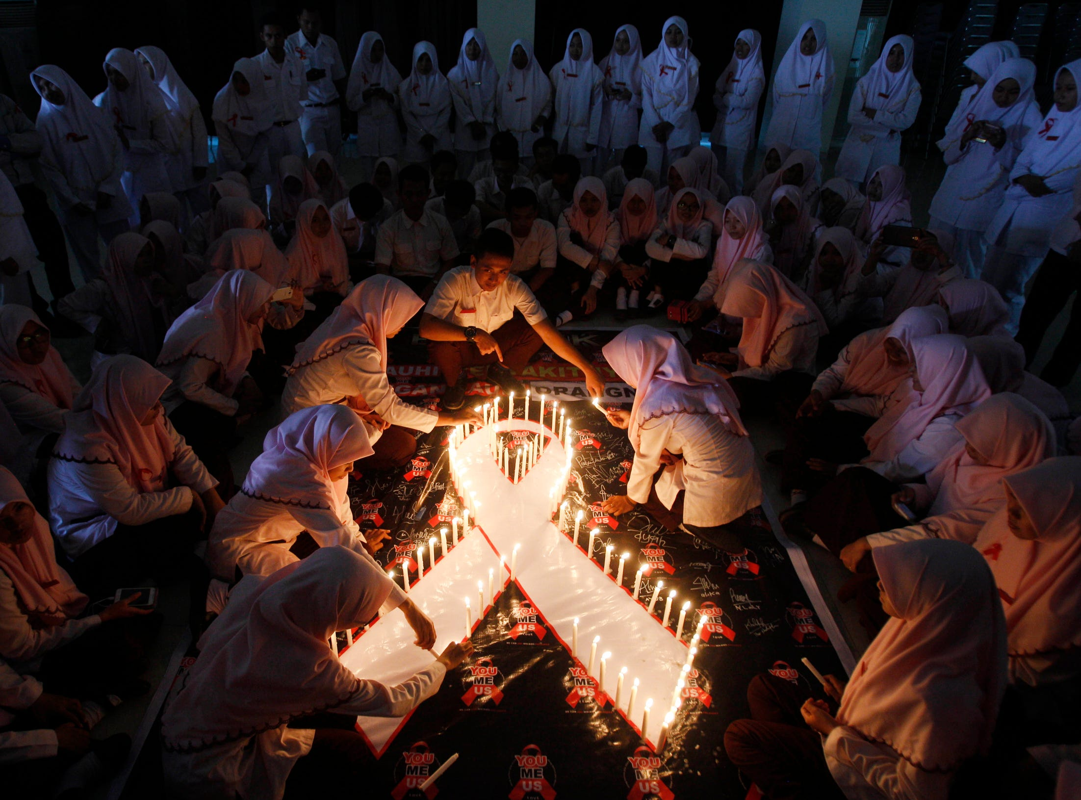 Indonesian medical students light candles during a vigil commemorating World AIDS day in Surabaya, East Java, Indonesia,  2015.