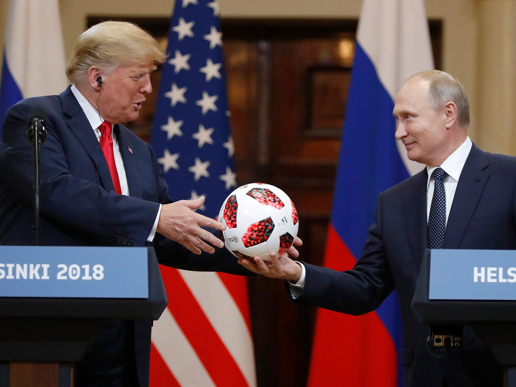 Russian President Vladimir Putin gives a soccer ball to U.S. President Donald Trump, left, during a press conference after their meeting at the Presidential Palace in Helsinki, Finland, Monday, July 16, 2018.