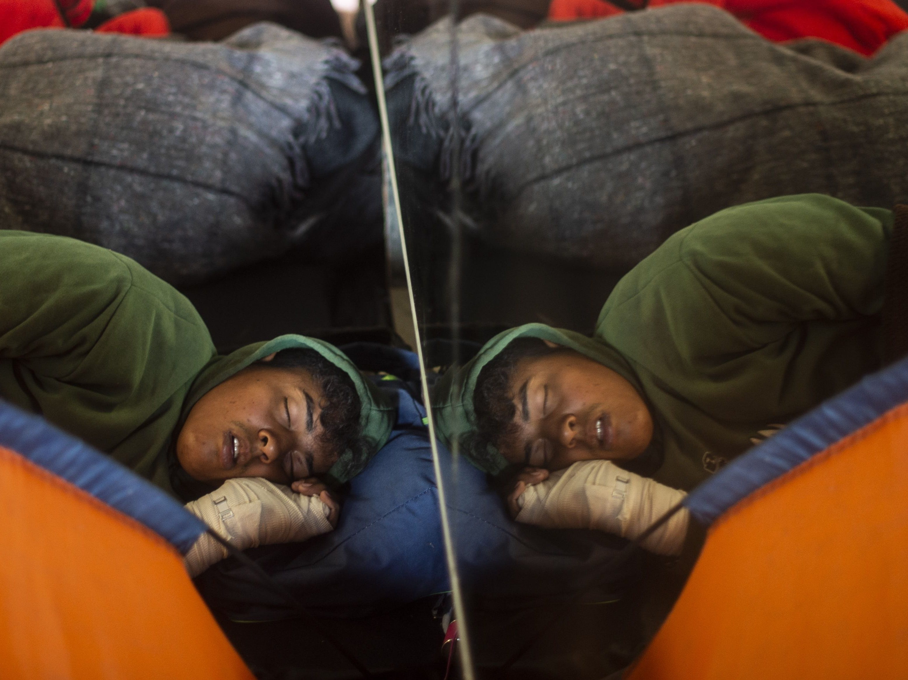 Central American migrants -mostly from Honduras- traveling in a caravan to the United States, rest after being relocated at a new temporary shelter in east Tijuana, Baja California State, Mexico, in the border with the US on Nov. 30, 2018.