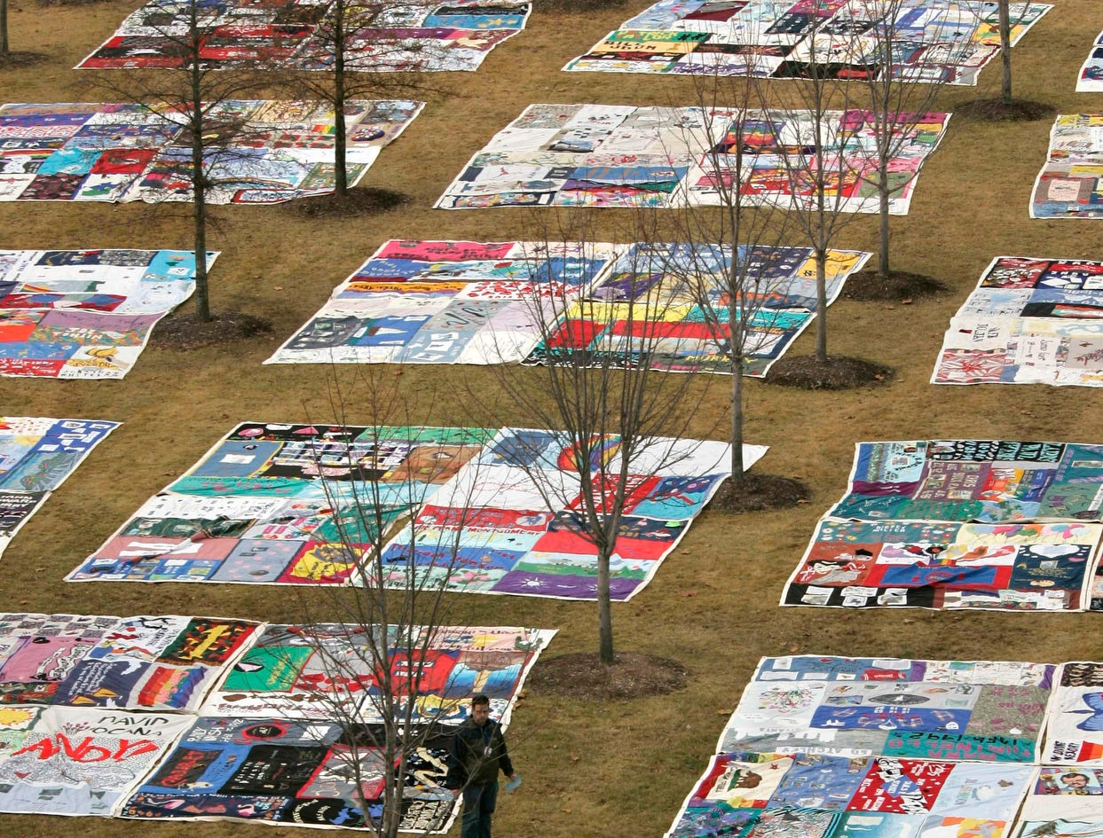 Volunteers unfurl a section of the AIDS memorial quilt on the lawn of the Clinton Presidential Library in Little Rock, Ark., in observance of World AIDS Day, Dec. 1, 2009.