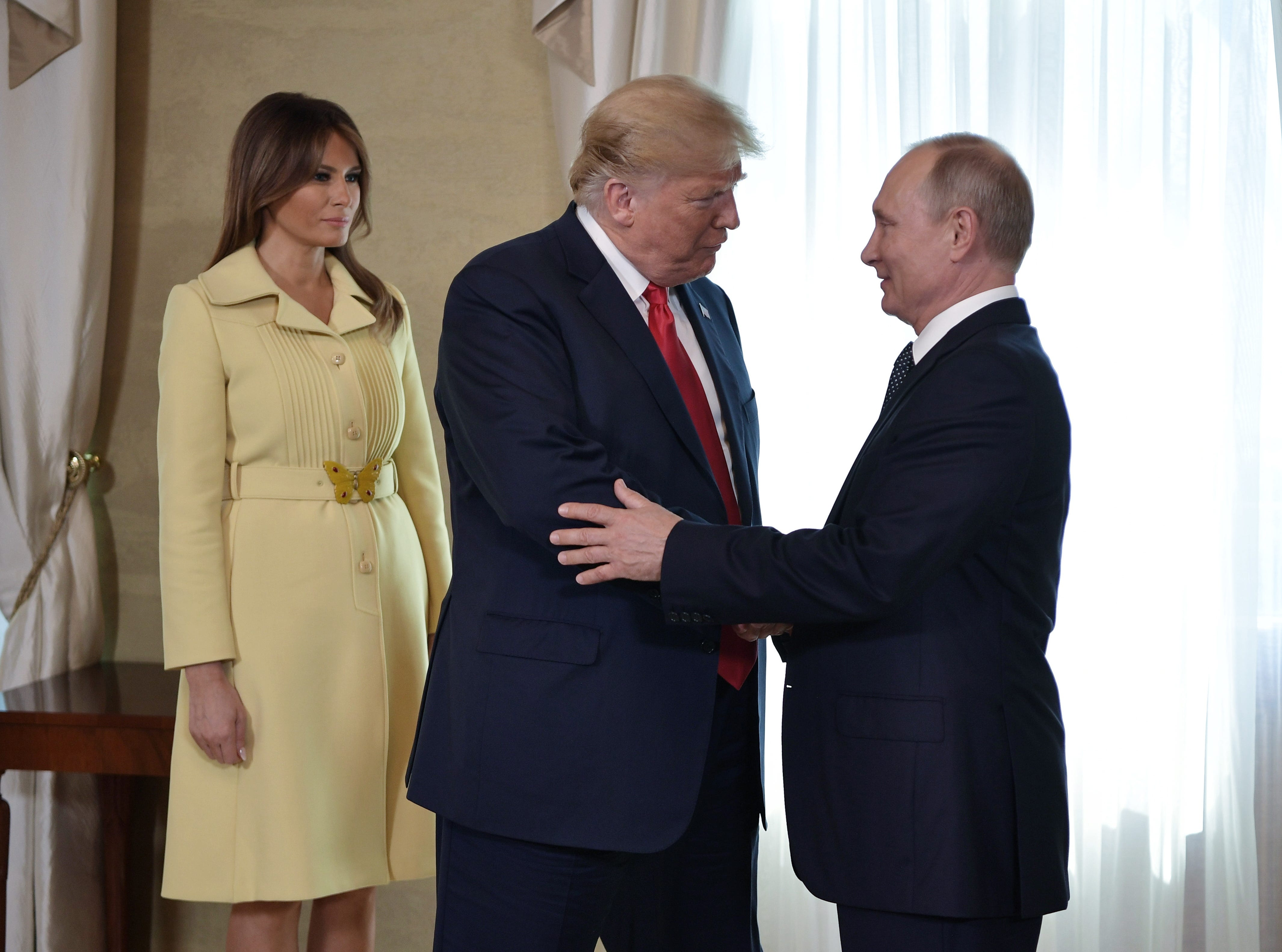Russian President Vladimir Putin and  US President Donald J. Trump shake hands  as First Lady Melania Trump looks on during their meeting at the Presidential Palace in Helsinki, Finland on July 16, 2018.