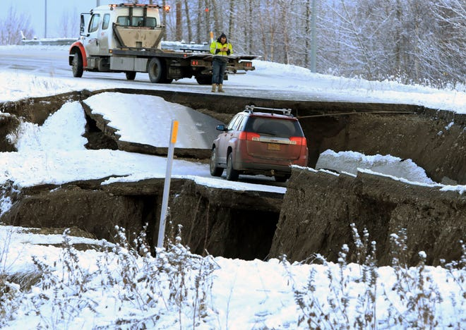 A tow truck driver assesses a car stuck on a section of an off-ramp that collapsed during an earthquake Friday morning, Nov. 30, 2018 in Anchorage, Alaska. The driver was not injured attempting to exit Minnesota Drive at International Airport Road.
