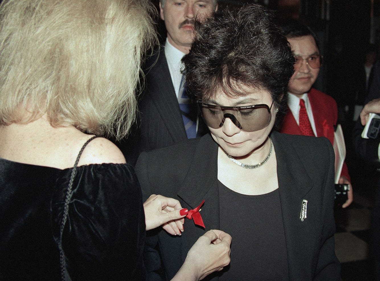 "Yoko Ono, wife of the late John Lennon, has a red  ""Aids Ribbon""  placed on her lapel during an American Foundation for Aids Research fund raiser at New York's Waldorf Astoria Hotel on Dec. 1, 1992.   The event was held in observance of World Aids Day."