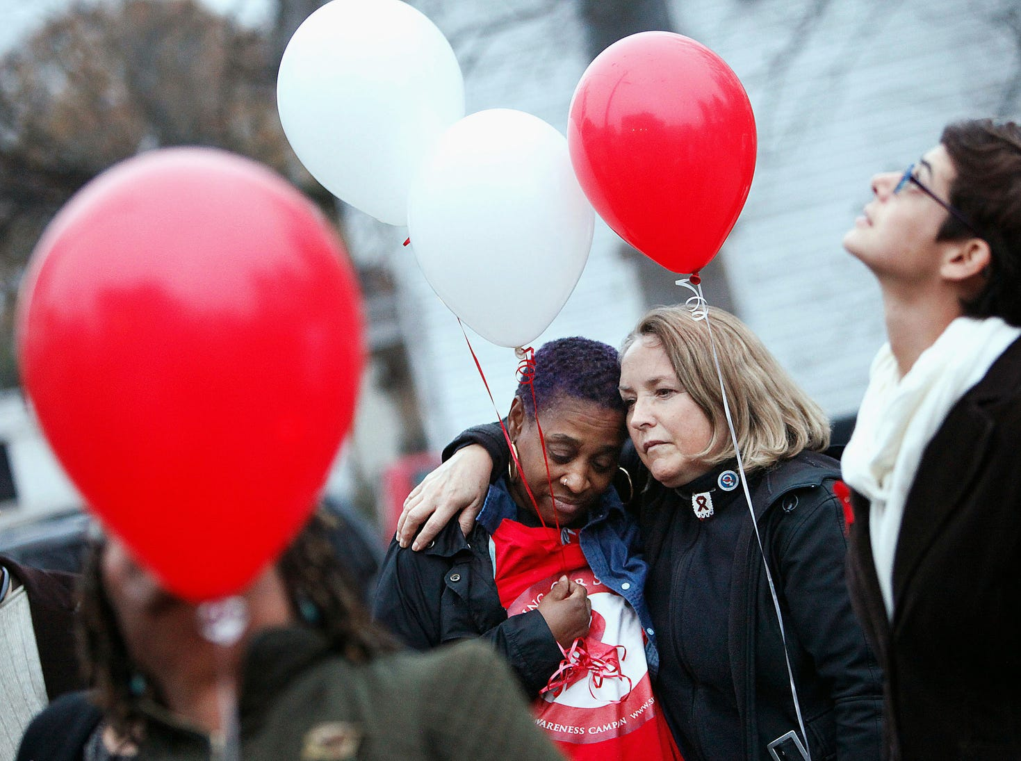 "Angela Vick, left, and Julieta Giner hug before releasing balloons to mark the 2015 World AIDS Day, in Durham, N.C. Vick, a motivational speaker, has been HIV-positive for nearly eight years. ""It's important to stop the stigma,"" Vick said."