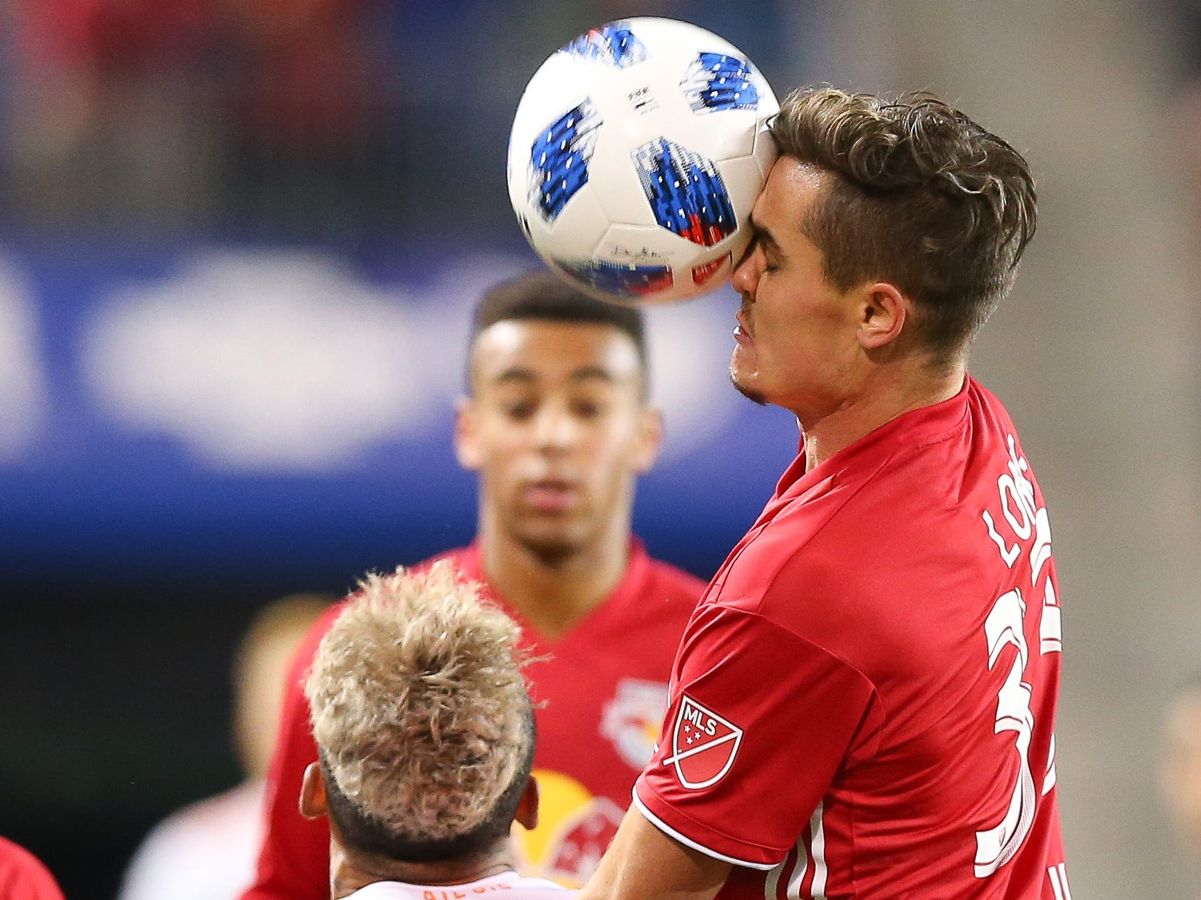 New York Red Bulls midfielder Aaron Long (33) heads the ball over Atlanta United forward Josef Martinez (7) during the first half of the second leg of the MLS Eastern Conference Championship at Red Bull Arena.