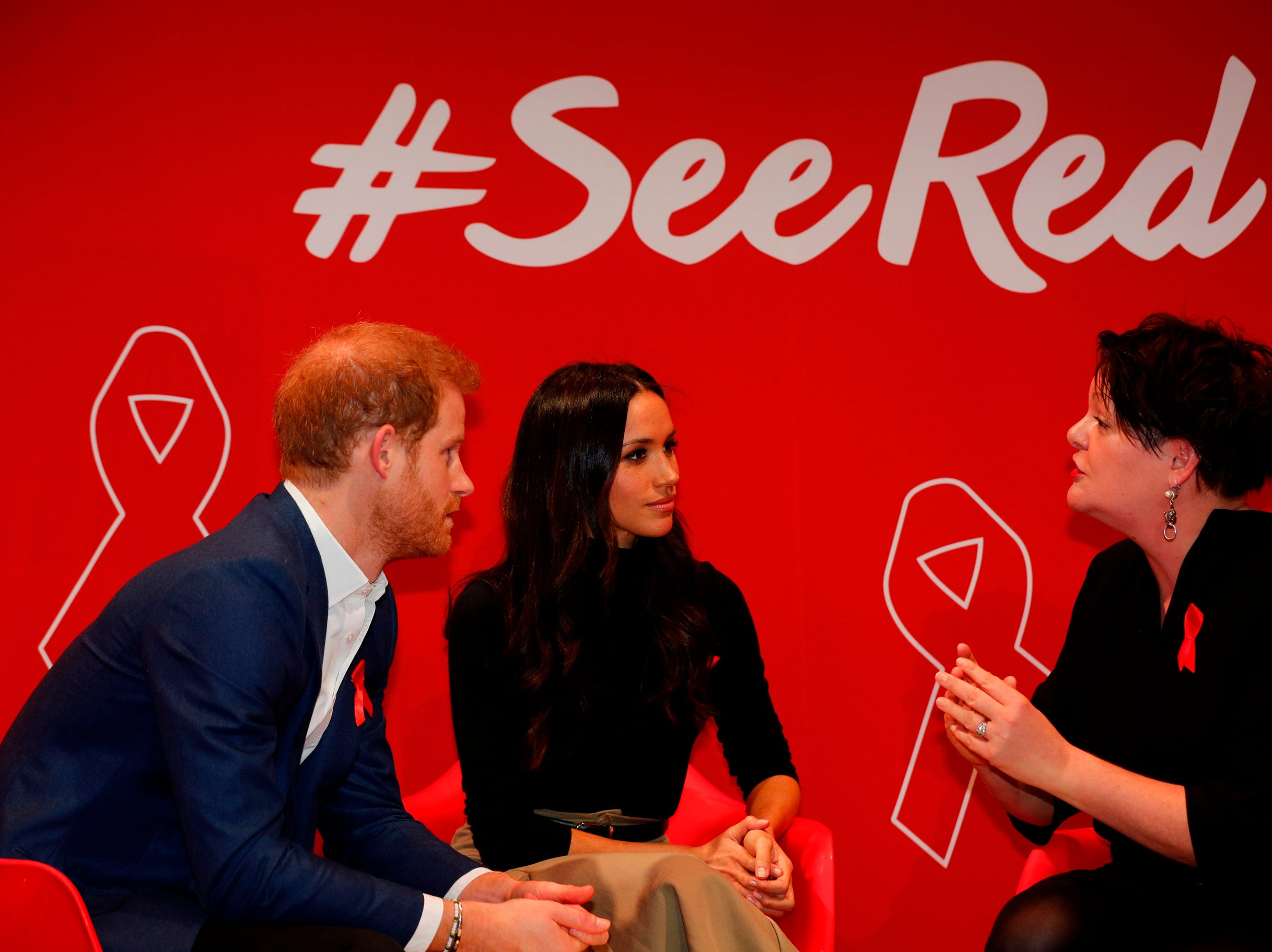 Britain's Prince Harry and his fiancee US actress Meghan Markle gesture as they tour the Terrence Higgins Trust World AIDS Day charity fair at Nottingham Contemporary in Nottingham, central England, on Dec. 1, 2017.