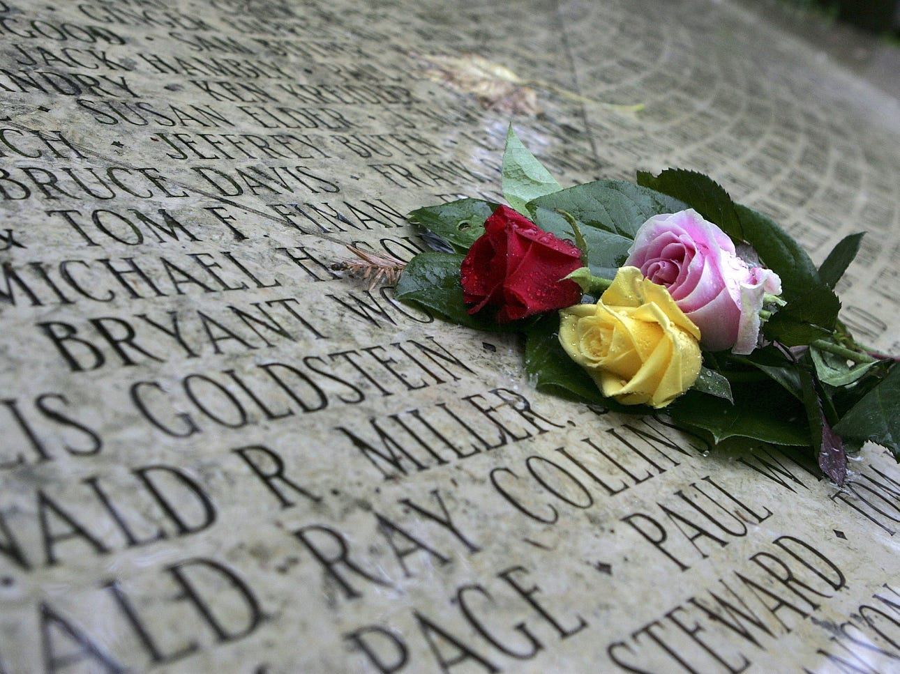 "Roses lie on the ""Circle of Friends,"" a ring of names engraved in stone to honor those who have died from AIDS at the AIDS Memorial Grove on World AIDS Day in 2005, in San Francisco."