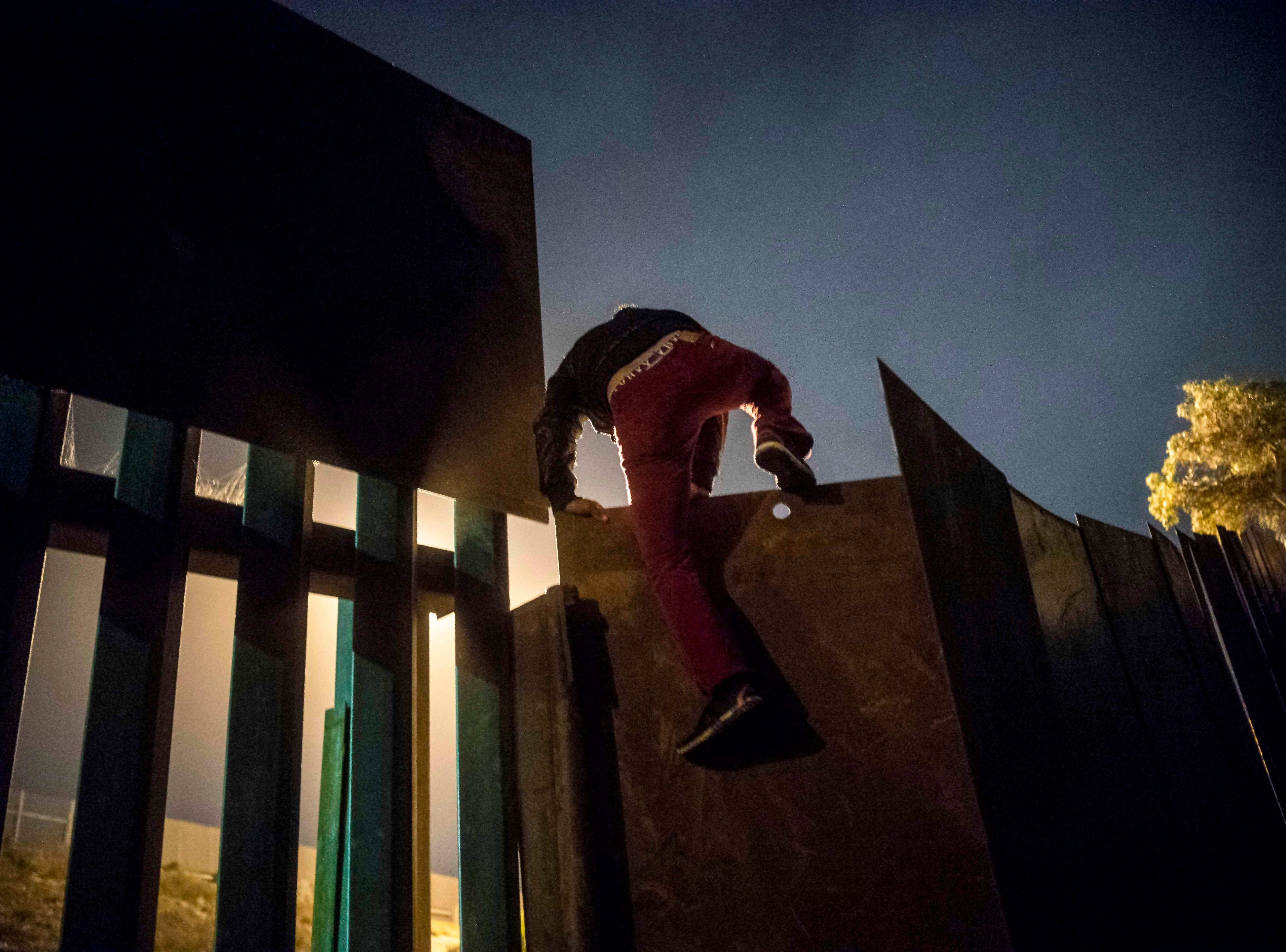 A Central American migrant who trekked for over a month across Central America and Mexico with a caravan in the hopes of reaching the United States, climbs the US-Mexico border fence to cross illegally from Playas de Tijuana, Baja California State, Mexico, to San Diego, Calif., US, on Nov. 30, 2018.