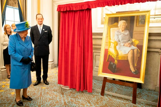 Queen Elizabeth II unveils a portrait of herself by artist Benjamin Sullivan and commissioned to celebrate 100 years of the RAF Club during a visit to the club to mark its centenary year in London on October 17, 2018. -