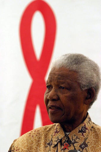 On Dec. 1, 2003 Nobel Peace Prize winner and iconic political prisoner Nelson Mandela talks to doctors and medical staff at the CF Jooste hospital in Cape Town, South Africa, on World AIDS Day. Many  African country leaders struggled with the truth of the AIDS epidemic.